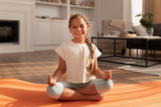 Full shot smiley mädchen meditiert auf yogamatte