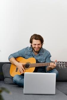 Full shot smiley mann mit gitarre Kostenlose Fotos