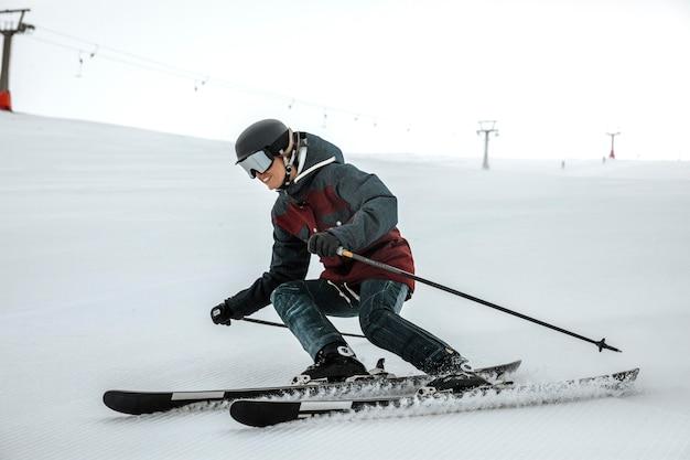 Full shot smiley skifahrer mit ausrüstung
