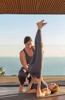 Full shot yogalehrerin hilft frau
