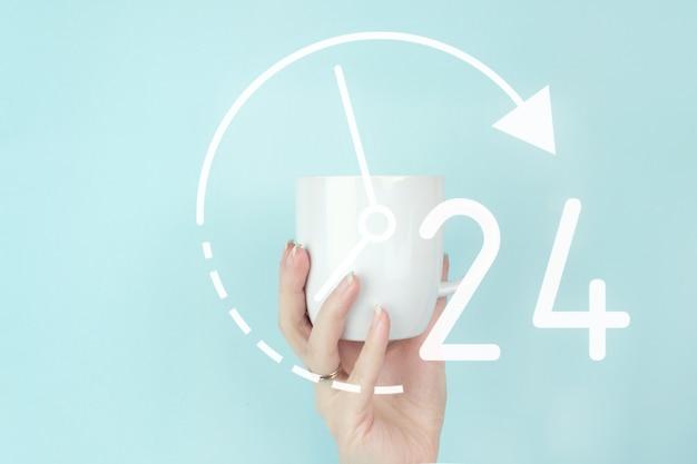 Full-time-service-konzept. ausgeschnittene ansicht der weiblichen hand mit weißer kaffeetasse und zeichensymbol auf blauem hintergrund. business-button 24-stunden-service