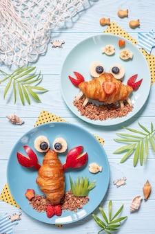 Fun food für kinder. niedliche krabben- und hummercroissants mit obst für kinderfrühstück