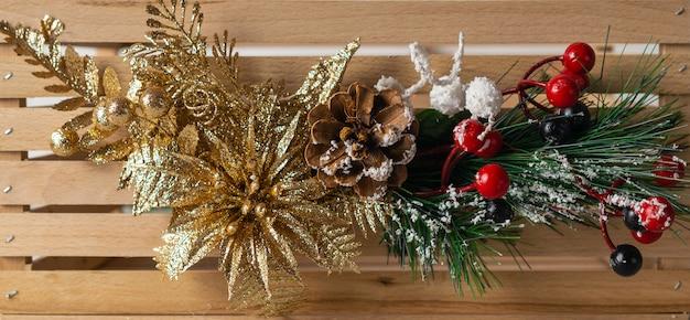 Funkelnde dekorative fahne chrismas auf holz mit tannenbaumasten und goldener blume