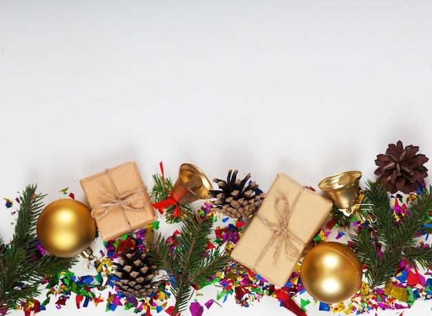 Funkelnde dekorative verzierung von tannenzweigen, zapfen, geschenken, weihnachtskugeln und glitzer auf weiß von weihnachten und neujahr