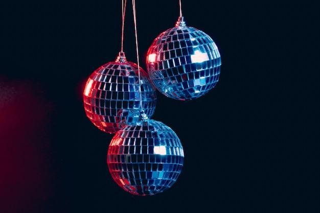 Funkelnde discokugeln, die in der luft gegen schwarzen hintergrund hängen