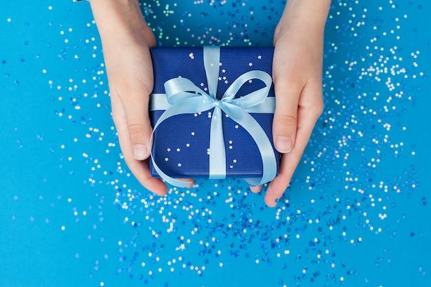 Funkelnde geschenkbox in bastelpapier eingewickelt und mit schleife in kinderhänden gebunden