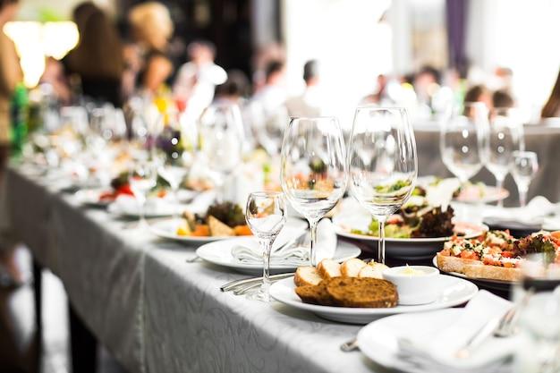 Funkelnde glaswaren stehen auf dem langen tisch, der für hochzeit di vorbereitet wird