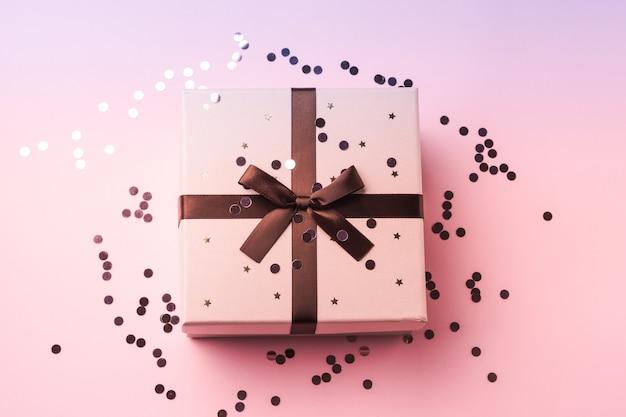 Funkelnde konfettis und geschenkbox auf rosa lila