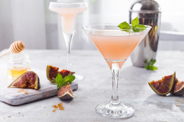 Funkelnder rosa limonade martini mit feigen und honig auf hellem hintergrund über fenstern