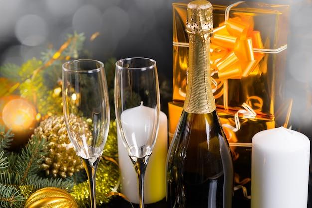 Funkelndes festliches stillleben - antike taschenuhr, die am hals einer champagnerflasche hängt, umgeben von eleganten gläsern, weißen stumpenkerzen, goldverpackten geschenken und festlichen evergreens