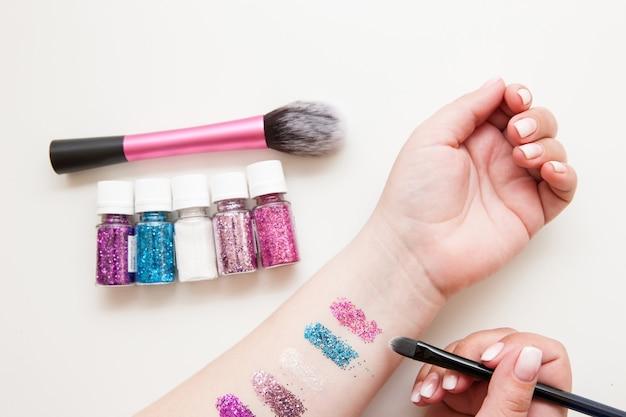 Funkelndes glitzermuster zur hand. make-up-sucht, einhorn-trend, glamour-lidschatten-konzept