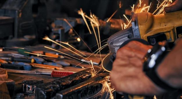 Funken, die mit einem elektrischen scheibenschleifer erzeugt werden, der das oberflächenmetall poliert