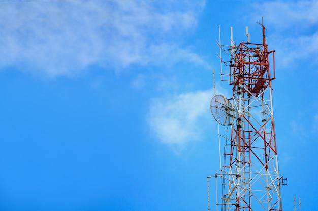 Funktechnologie des telekommunikationsturms und der satellitenantennen auf blauem himmel