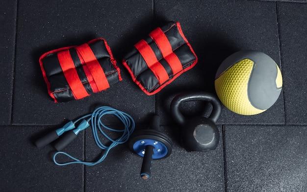 Funktionelle trainingsgeräte. kettlebell und springseil, bauchrolle, medizinball, massagerolle, gewichte auf einem dunkelschwarzen boden. bodybuilding und fitness