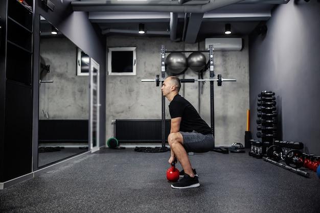 Funktionelles cross-fit-körpertraining mit einer kettlebell. ein porträt eines mannes in sportkleidung mit einem schwarzen t-shirt, das mit gespreizten beinen steht und ein indoor-fitnessstudio mit kettlebell anhebt. körperliche ausdauer