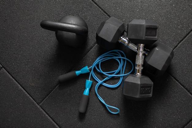 Funktionelles training sportgeräte. kettlebell und springseil, hanteln auf einem dunkelschwarzen boden. bodybuilding und fitness