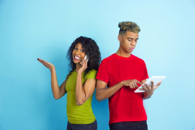 Funktioniert auf dem tablet, telefoniert. junger emotionaler afroamerikanischer mann und frau in den bunten kleidern auf blauem hintergrund. schönes paar. konzept der menschlichen emotionen, gesichtsausdruck, beziehungen, anzeige.