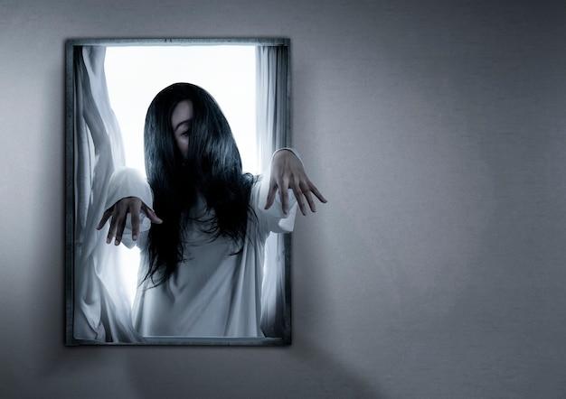 Furchterregende geisterfrau, die auf dem fenster im verlassenen haus steht. halloween-konzept