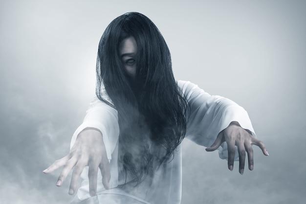 Furchterregende geisterfrau, die im nebel-halloween-konzept kriecht