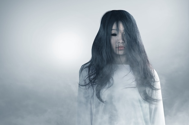 Furchterregende geisterfrau, die im nebel-halloween-konzept steht