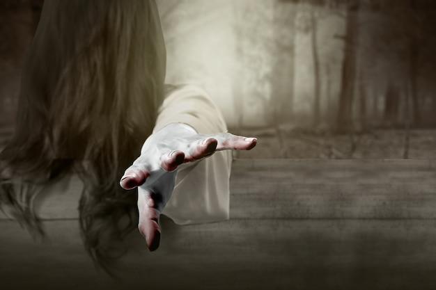 Furchterregende geisterfrau, die mit verfolgtem wald steht