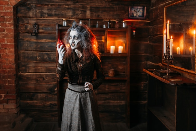Furchterregende hexe hält menschliches herz am spiegel und kerzen, dunkle kräfte der hexerei, spirituelle seance. die weibliche vorfahrin nennt die geister die schreckliche zukunftserzählerin