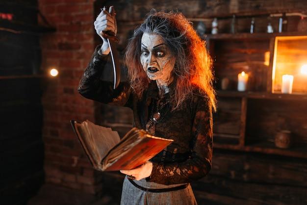 Furchterregende hexe hält zauberbuch und messer, dunkle kräfte der hexerei, spirituelle seance.