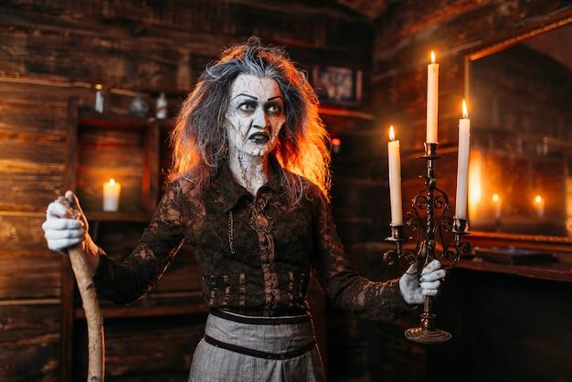 Furchterregende hexe mit einem kerzenhalter und einem stock liest mystischen zauber, spirituelle seance. die weibliche voraussagerin nennt die geister eine schreckliche wahrsagerin