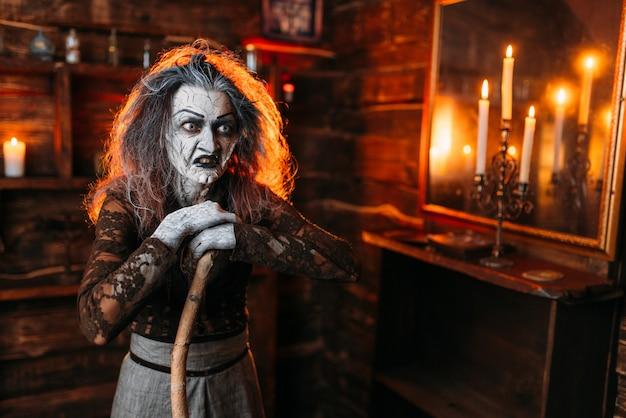 Furchterregende hexe mit einem stock am spiegel und kerzen, dunklen kräften der hexerei, spiritueller seance. die weibliche voraussagerin nennt die geister eine schreckliche wahrsagerin