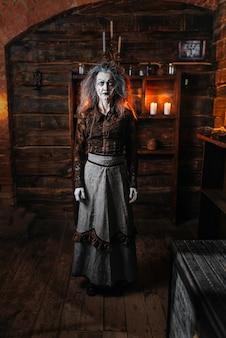 Furchterregende hexe steht auf einem stock, seance