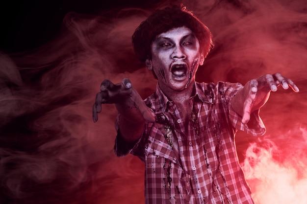 Furchterregende zombies mit blut und wunden auf seinem körper, die durch den dunklen nebel laufen