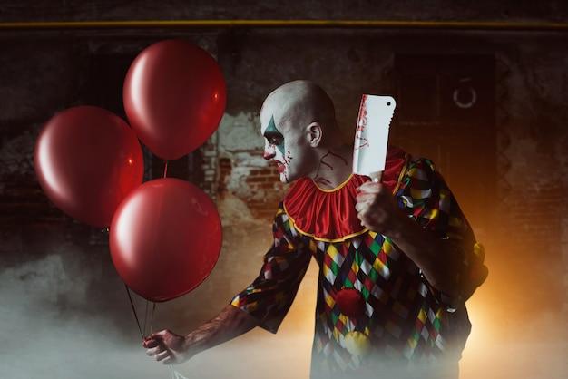 Furchterregender blutiger clown mit fleischbeil und luftballon, der sich entsetzt in den keller schleicht. mann mit make-up im karnevalskostüm, verrückter verrückter