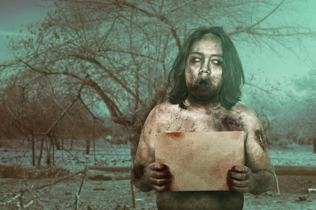 Furchterregender zombie mit blut und wunde an seinem körper, der ein leeres brett hält