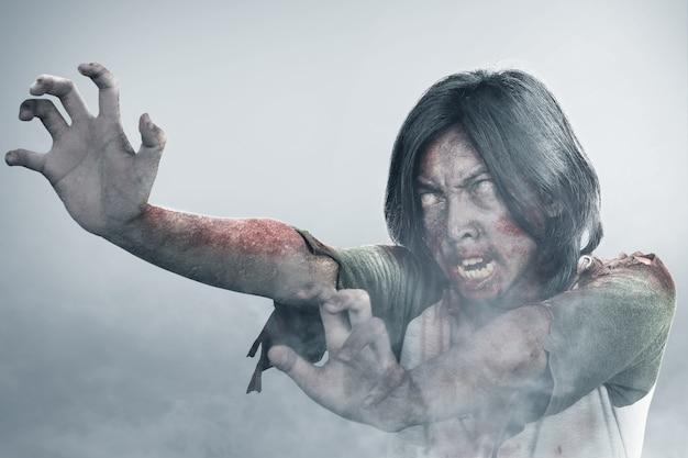 Furchterregender zombie mit blut und wunde an seinem körper, der im nebel läuft
