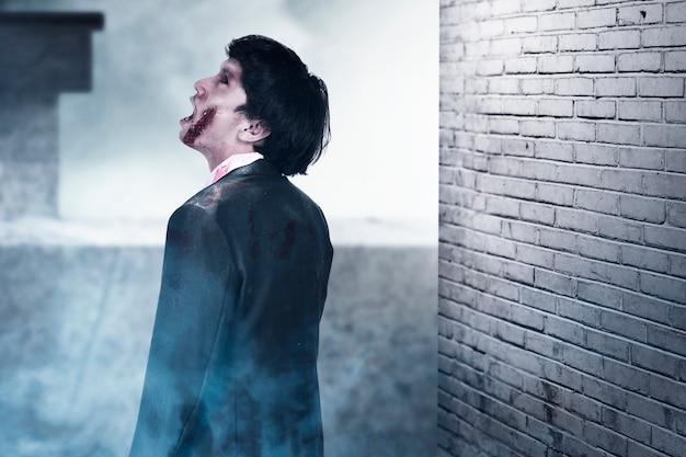 Furchterregender zombie mit blut und wunde an seinem körper, der in dem verlassenen gebäude steht
