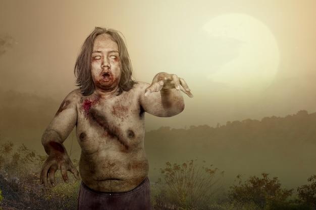 Furchterregender zombie mit blut und wunde auf seinem körper, der auf dem feld geht