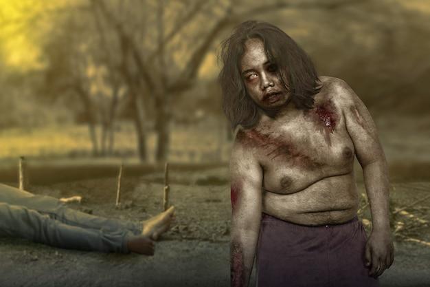 Furchterregender zombie mit blut und wunden am körper mit einem toten auf dem feld