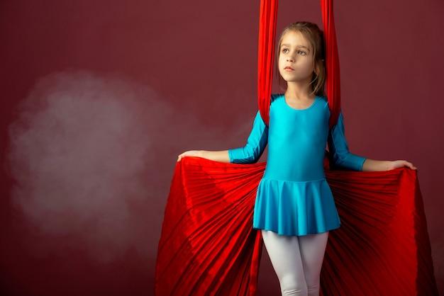 Furchtloses hübsches kleines mädchen in einem blauen turnanzug