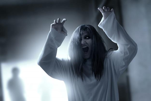 Furchtsame geistfrau mit blut und verärgertem gesicht mit den greiferhänden frequentierte das verlassene gebäude