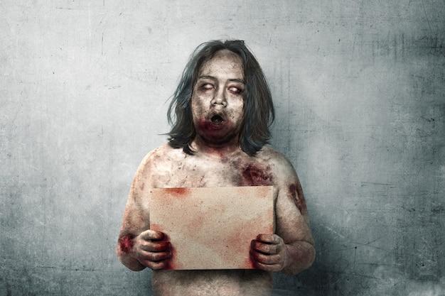 Furchtsame zombies mit blut und wunde auf seinem körper, der ein schild hält