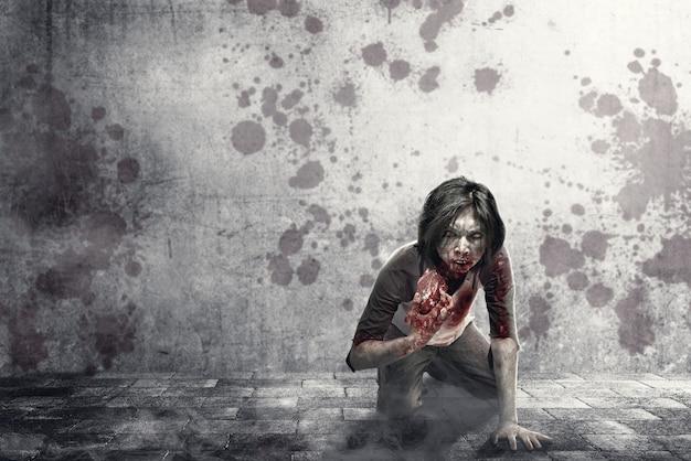 Furchtsame zombies mit blut und wunde auf seinem körper, die das rohe fleisch auf der städtischen straße essen