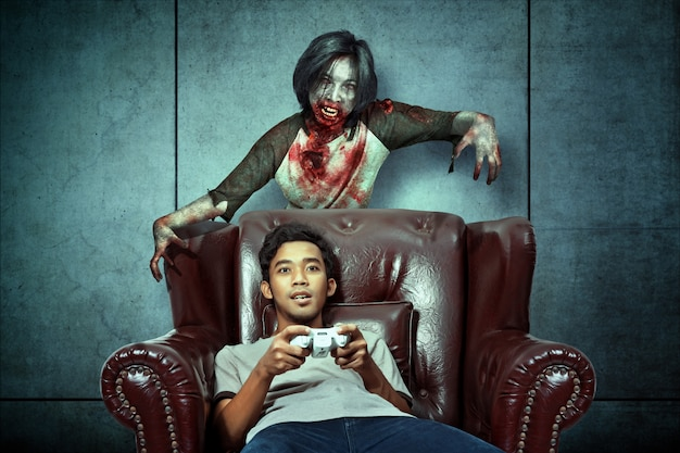Furchtsame zombies verfolgten asiatische männer, während sie auf der couch spielten