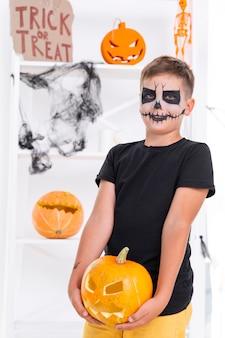 Furchtsamer junge, der halloween-kürbis hält