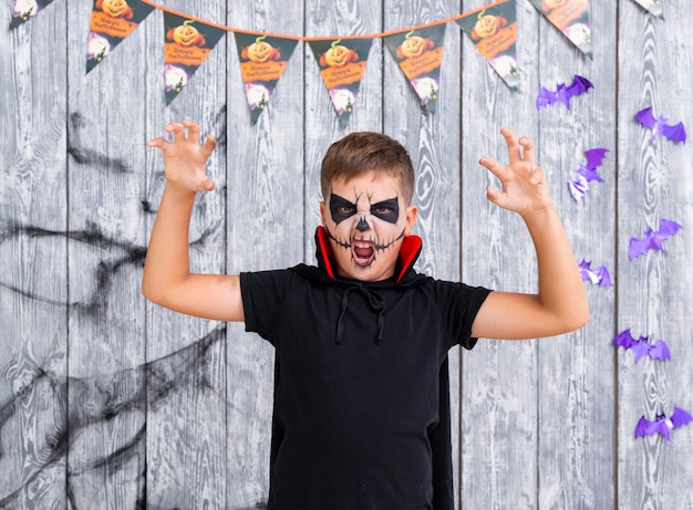 Furchtsamer junge mit dem gesicht gemalt für halloween