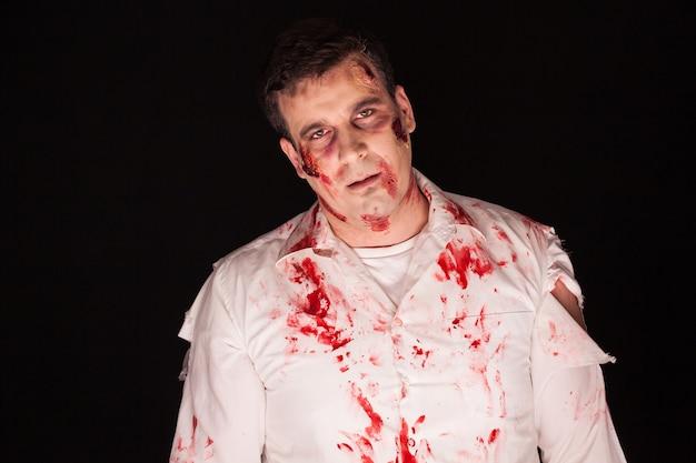 Furchtsamer und blutiger zombie über schwarzem hintergrund. halloween-outfit.