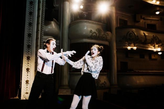 Furchtsamer weiblicher pantomime, der versucht, sich vom männlichen pantomimen im auditorium zu verteidigen