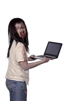 Furchtsamer weiblicher zombie, der laptop hält