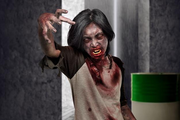 Furchtsamer zombiemann mit den händen für das kratzen auf dem dunklen platz