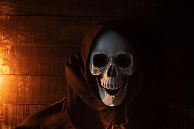 Furchtsames skelett des halloween-kostümgeistes, das einen mit kapuze mantel trägt