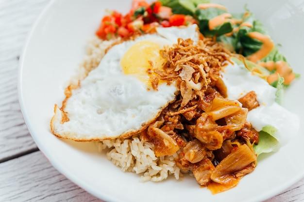 Fuselahrungsmittel reisschüsselbelag kimchi-schweinefleisch, organisches spiegelei, koreanische aubergine und salat.